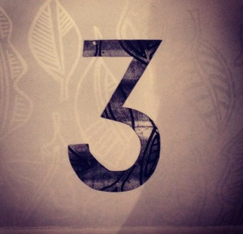 Table number. White linocut printed on white paper with a black number.